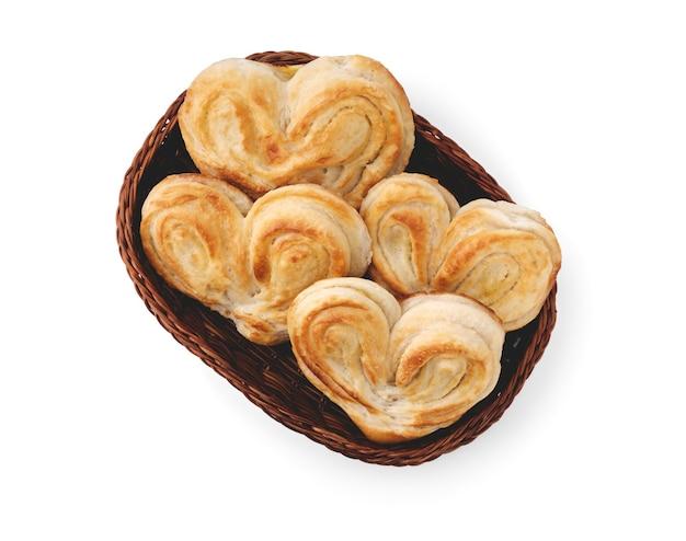 Les petits pains sucrés en forme de coeur se trouvent dans un panier dans un style plat isolé sur fond blanc propre.