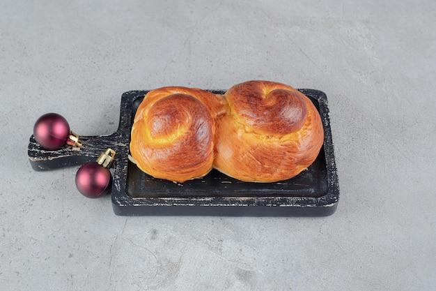 Petits pains sucrés sur un petit plateau sur table en marbre.
