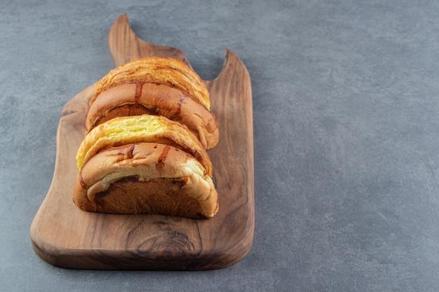 Petits pains sucrés placés sur planche de bois.