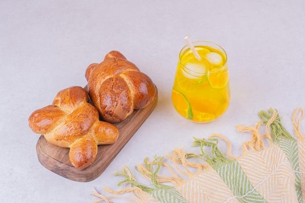 Petits pains sucrés sur plateau en bois avec un verre de limonade.
