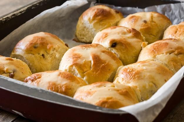 Petits pains traditionnels de pâques chauds dans une plaque de four sur une table en bois