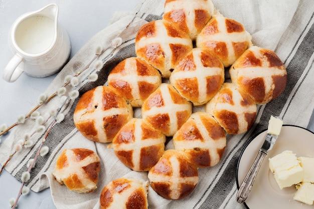 Petits pains traditionnels de pâques faits maison sur un plateau en bois avec du textile en lin et des branches de saule sur une vieille pierre ou un fond en béton. mise au point sélective. vue de dessus. copiez l'espace.