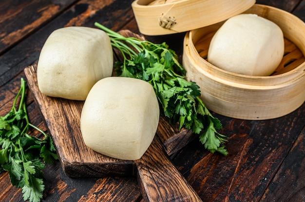 Petits pains à la vapeur chinois bao. fond en bois sombre. vue de dessus.