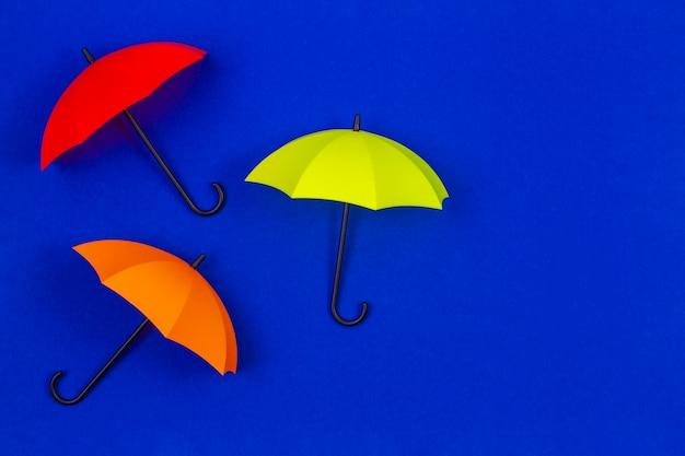 Petits parapluies colorés sur la couleur bleue