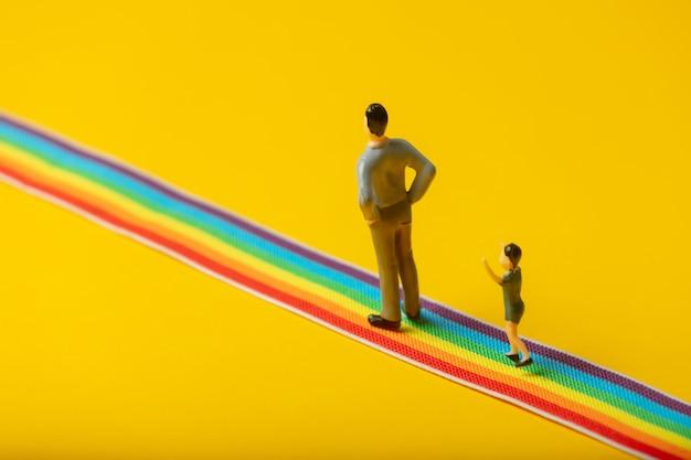 Petits personnages père et fils sur le chemin arc-en-ciel lgbt