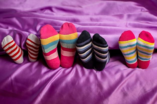 Petits pieds dans des chaussettes colorées. pieds d'enfants portant des chaussettes colorées. couverture violette et chaussettes rayées. portez ce que vous voulez.