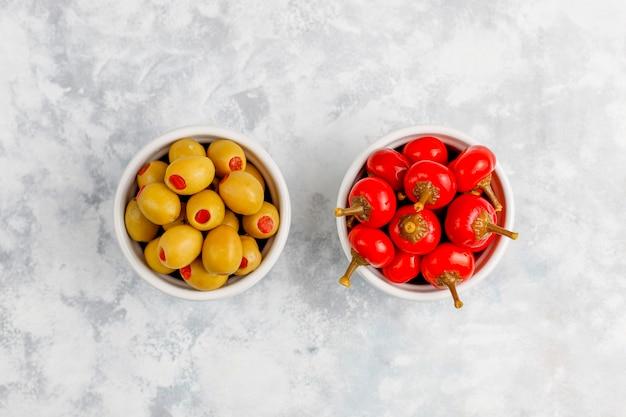 Petits piments rouges cerises piquants sur du béton gris mariné
