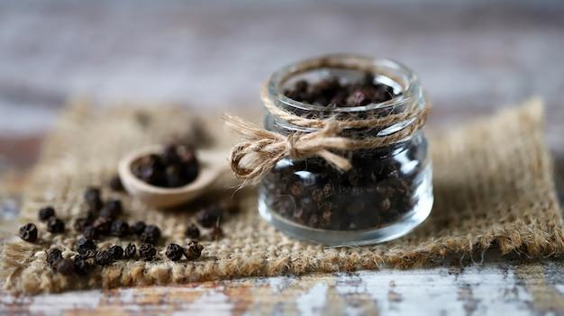 Petits pois au poivre noir. poivre noir dans un pot et dans une cuillère en bois.