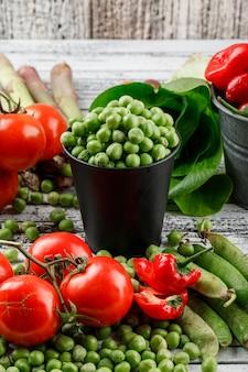 Petits pois dans un mini seau avec poivrons, tomates, asperges, bok choy, gousses vertes vue en plongée sur un mur en bois grungy