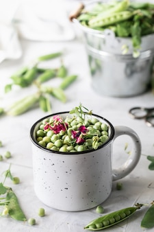 Petits pois verts dans une casserole sur blanc