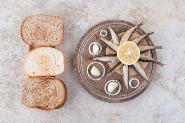 Petits poissons fumés et tranches de pain sur planche de bois