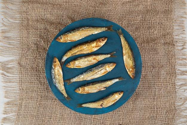 Petits poissons séchés sur plaque bleue