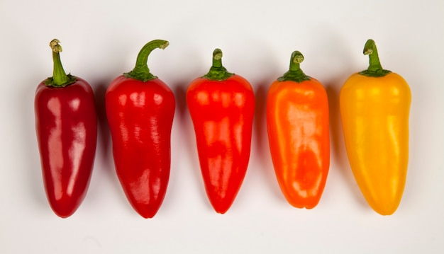 Petits poivrons épicés créant un gradient de couleur du rouge foncé au jaune passant au rouge clair et à l'orange.