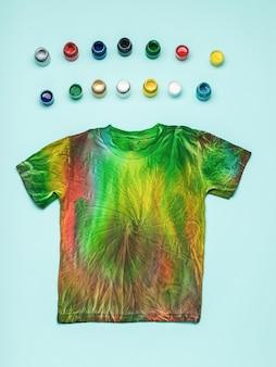 Petits pots de teintures textiles colorées et t-shirt tie dye sur fond bleu. mise à plat.