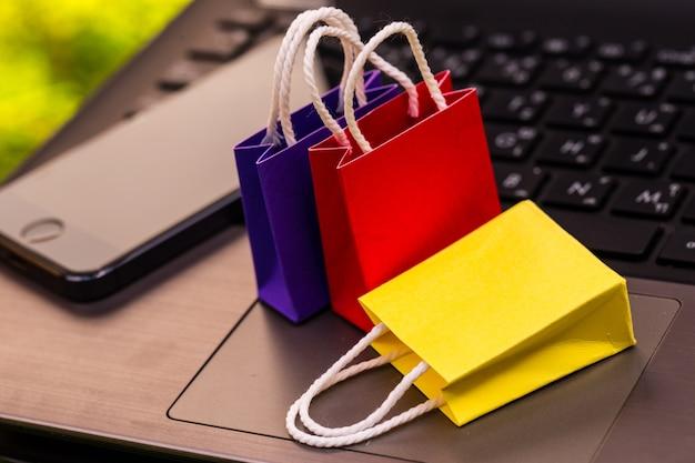 Petits sacs à provisions en papier avec téléphone portable sur un clavier d'ordinateur portable