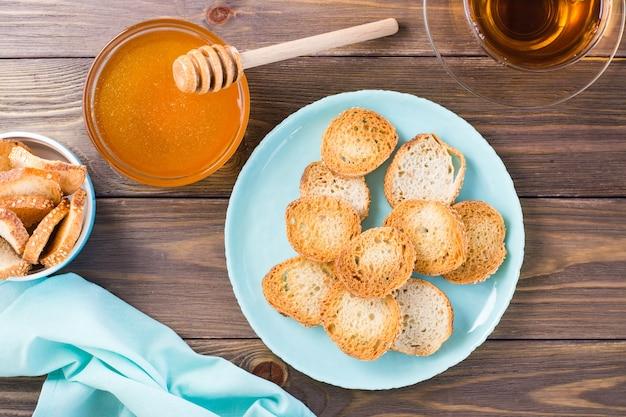 Petits toasts baguette sur une assiette sur une table en bois thé maison au miel