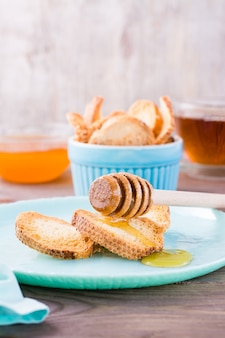 Petits toasts baguette au four avec du miel chaud sur une assiette sur une table en bois de thé fait maison gros plan