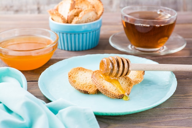 Petits toasts baguette au four avec du miel chaud sur une assiette sur une table en bois thé fait maison