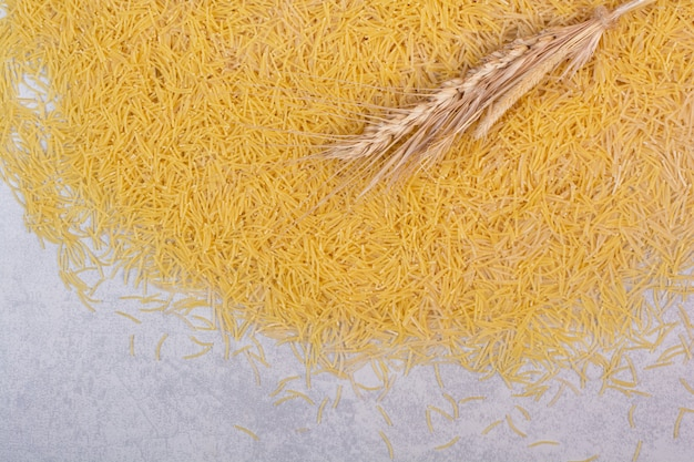 Petits vermicelles non cuits avec du blé sur une surface blanche