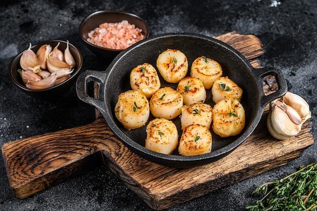 Pétoncles frits avec sauce au beurre dans une casserole.