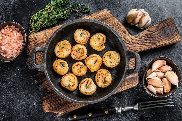 Pétoncles frits avec sauce au beurre dans une casserole