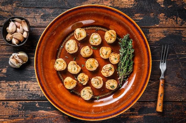 Pétoncles frits avec sauce épicée au beurre dans une assiette
