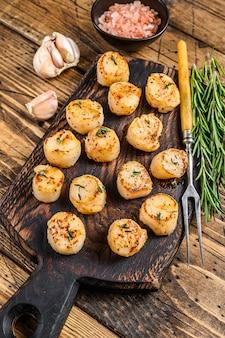Pétoncles poêlés au barbecue avec sauce au beurre sur une planche de bois