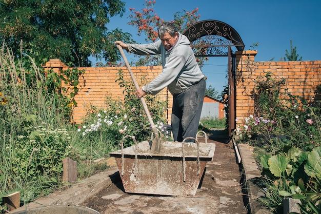 Pétrir du ciment pour couler un chemin de jardin, des travaux de construction de jardin.