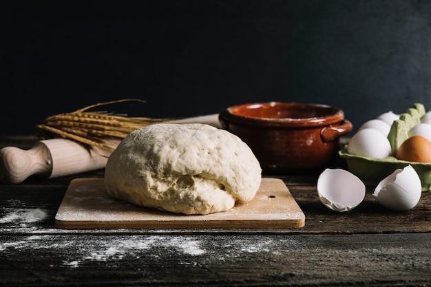 Pétrir la pâte avec des ingrédients sur une table en bois