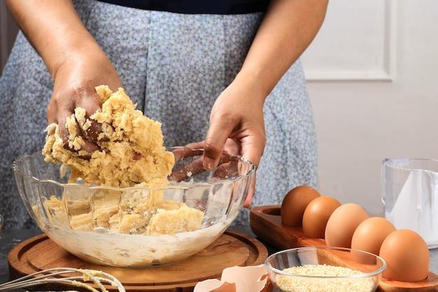 Pétrir la pâte à pain à la main des femmes dans un bol à mélanger, main nue