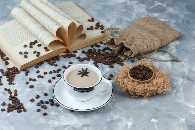 Un peu de café avec des grains de café, livre, sac dans une tasse sur fond de plâtre gris, vue grand angle.