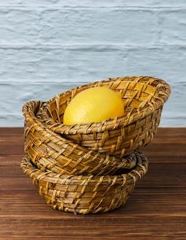 Un peu de citron dans un panier sur une surface en bois, vue grand angle. espace pour le texte