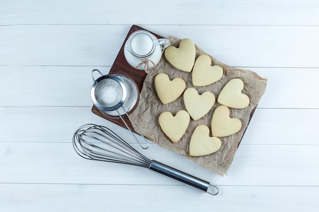 Un peu de lait avec des biscuits, du sucre en poudre, une passoire, un fouet dans une cruche sur fond blanc et planche à découper, vue de dessus.