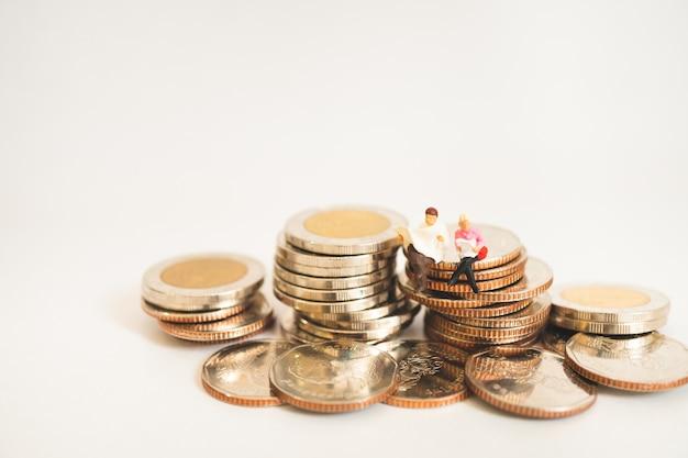 Peuple gens homme et femme assis sur des pièces de pile en utilisant comme affaires et finances concep