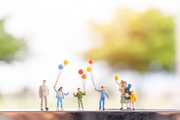 Peuple miniature: famille heureuse avec des ballons