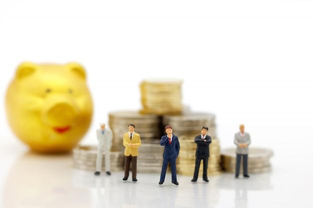 Peuple miniature: hommes d'affaires debout avec pile de pièces, finances, concept d'investissement.