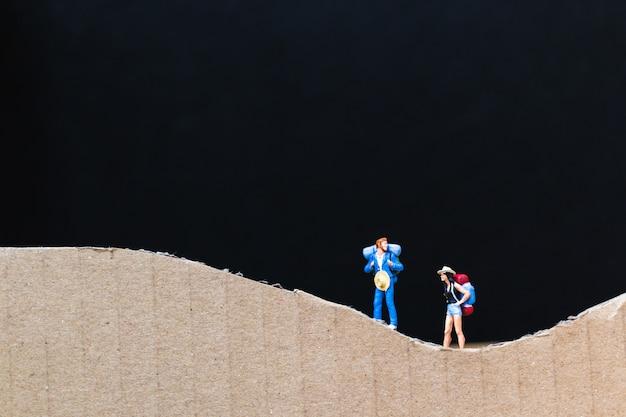 Peuple miniature: voyageur avec sac à dos marchant sur la montagne de papier