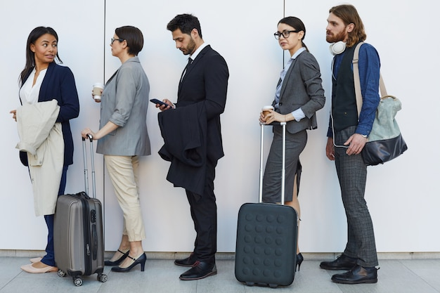Peuple multiethnique avec bagages debout en ligne