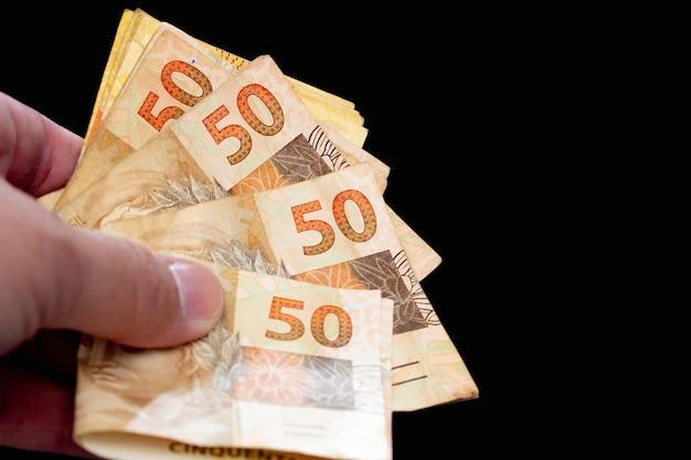 Un peuple tenant des billets de banque brésiliens de real brésilien