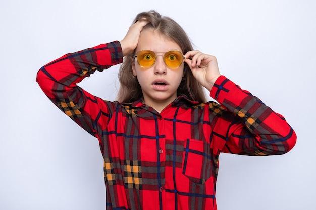 Peur a attrapé la tête belle petite fille portant une chemise rouge et des lunettes isolées sur un mur blanc