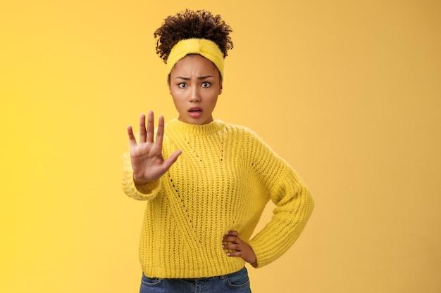 Peur, choquée, femme insécurisée essayant de montrer la voix être courageuse étendre le bras suffisamment arrêter le geste de refus sembler effrayée insécure, peu confiante, rejetant la proposition offensive en déclin, fond jaune.