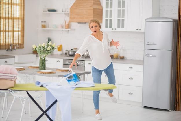 Peur de femme adulte blonde en chemisier blanc et jeans laissant le fer chaud sur