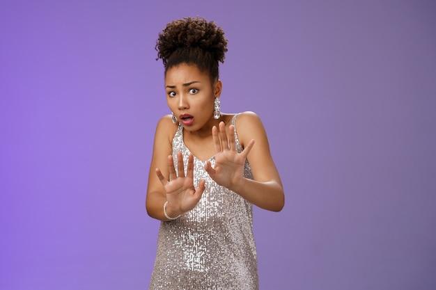 Peur d'une femme afro-américaine insécurisée implorant la miséricorde s'il vous plaît arrêtez de renverser un ami effrayé, buvez sa luxueuse robe coûteuse en argent levant les paumes effrayées écarquiller les yeux terrifiés en tremblant.