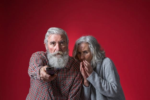 Peur femme assise près de l'homme senior changer de canal avec télécommande sur fond rouge