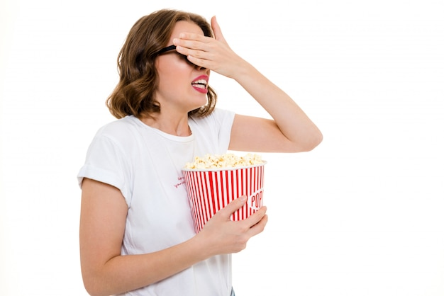 Peur femme caucasienne tenant le film de montre pop corn.