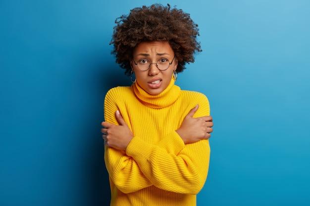 Peur de femme à la peau sombre garde les mains croisées, tremble de peur, porte des lunettes rondes et un pull jaune, isolé sur fond bleu