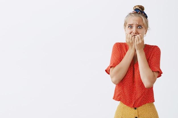 Peur et insécurité jeune fille blonde posant contre le mur blanc