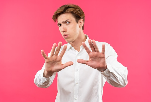 Peur de jeune beau mec vêtu d'une chemise blanche tendant les mains à la caméra isolée sur un mur rose