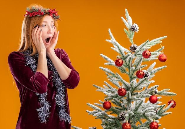 Peur jeune belle fille debout à proximité de l'arbre de noël vêtue d'une robe rouge et d'une couronne avec une guirlande sur le cou regardant l'arbre de noël mettant les mains sur les joues isolées sur le mur orange
