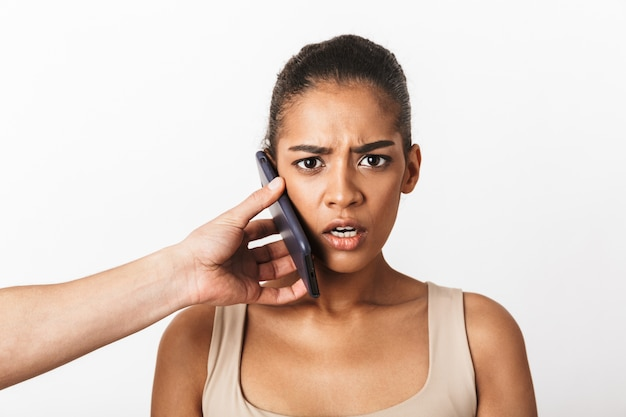 Peur de jeune femme africaine assise tandis que la main de l'homme tenant le téléphone portable à son oreille isolé sur blanc